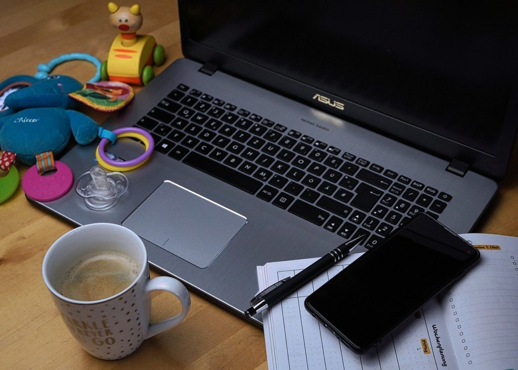 Picture of a laptop with coffee and a children's toy.