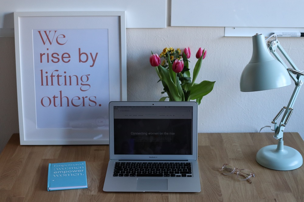 A laptop with a sign that says 'we rise by helping others'