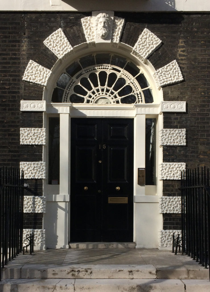 Photo of the Bedford Square doorway. Georgian style. Around the doorway itself, decorative stone panels are picked out in white against grey bricks.