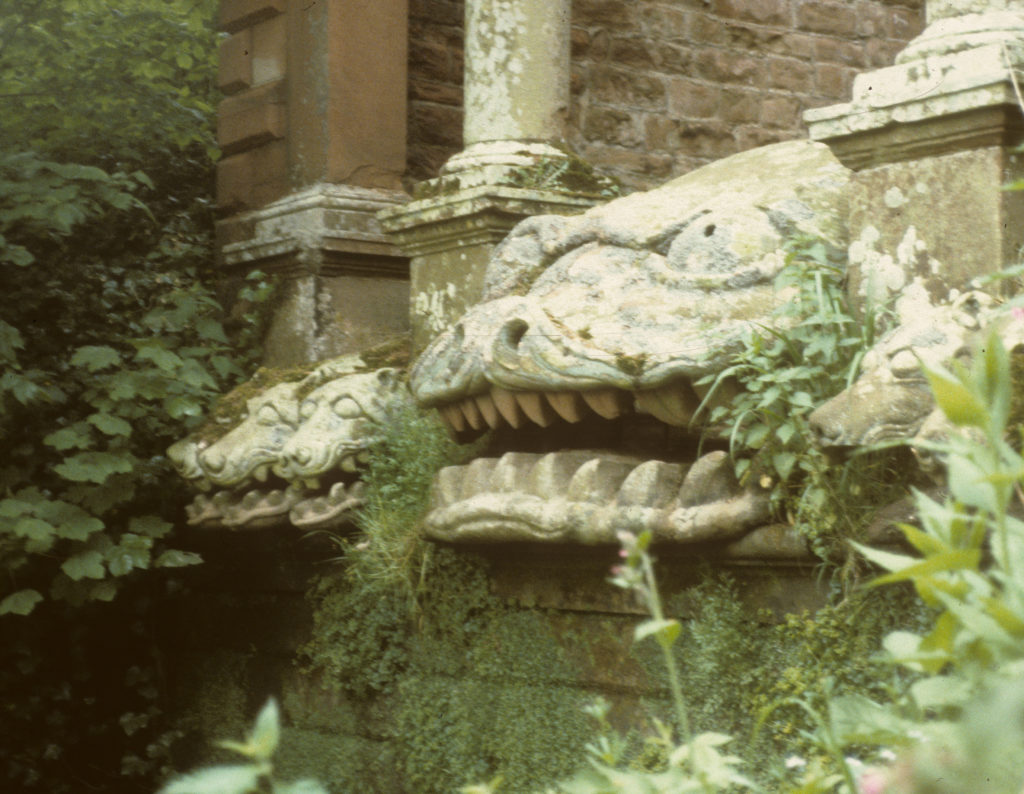 A photo of a large gargoyle next to three smaller ones.
