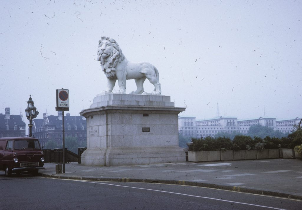 Photo of a central London street, in the 1950s or 60s. On a large plinth is a statue of a lion standing, looking out. An old Bedford type van is parked near it.