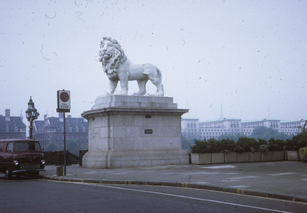 Photo of the Westminster Bridge lion, made in 1937. On a large plinth is a statue of a lion standing, looking out. An old Bedford type van is parked near it.