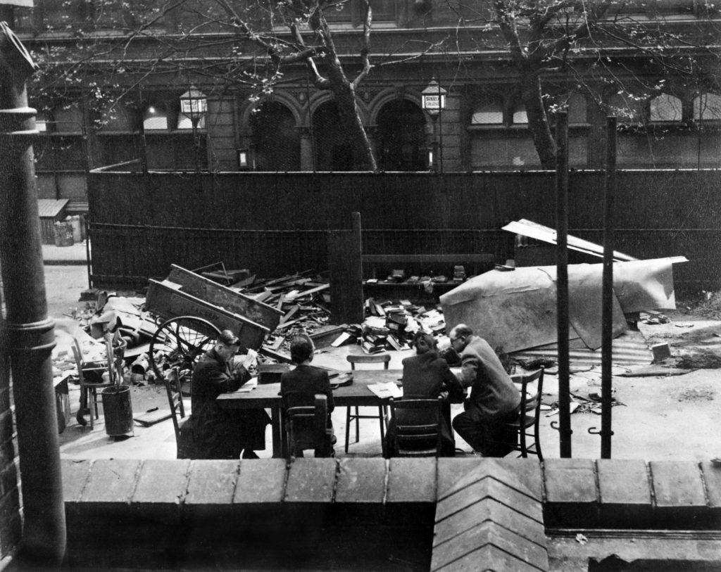 Four people are working at a table. The table is in a bombed out street.