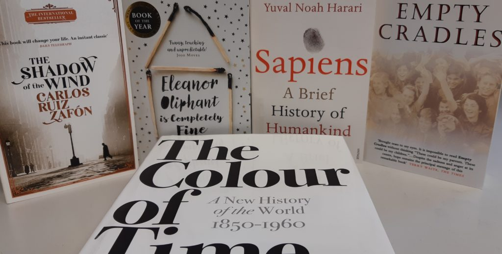 "Photo of five books in our reading for pleasure collection. The books are, ""The Shadow of the Winds', Eleanor Oliphant is Completely Fine', 'Sapiens', 'Empty Cradles', and 'The Colour of Time'."