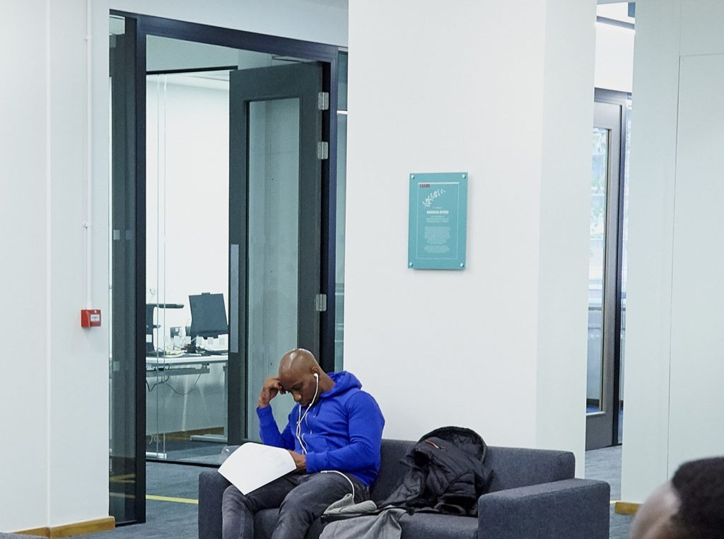 Photo of a black male student working in one of the silent study areas in the Library.