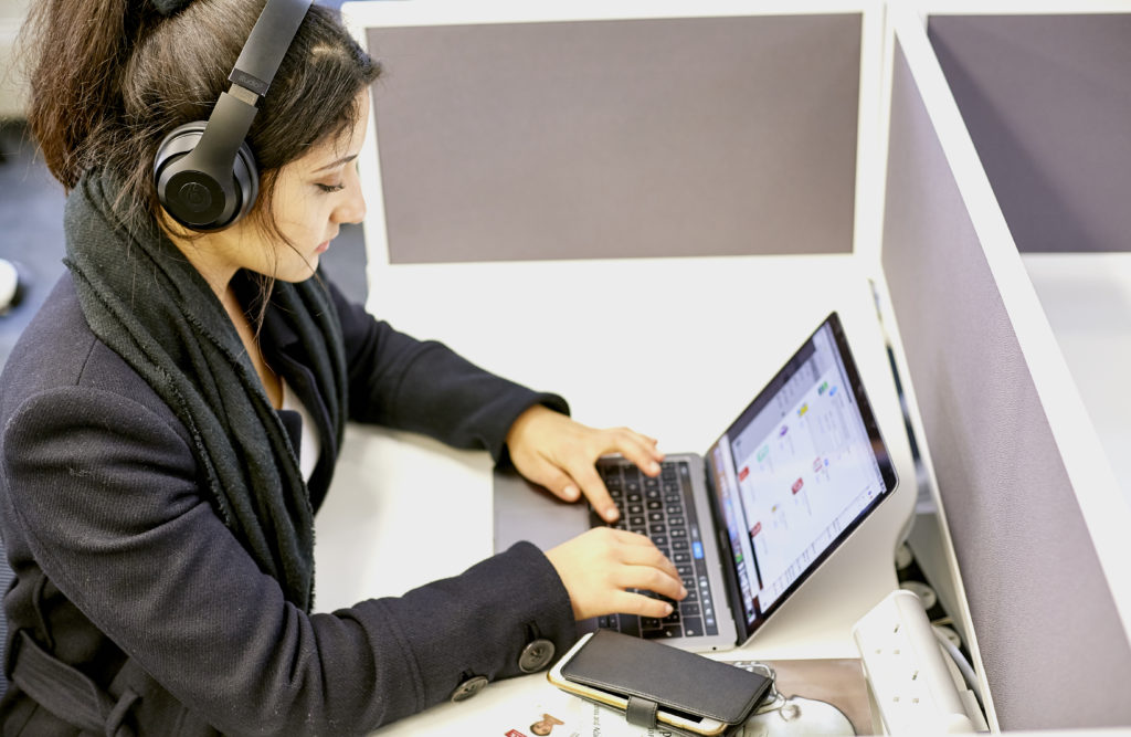 An asian woman student works at her laptop in one of the silent study areas of the Library.