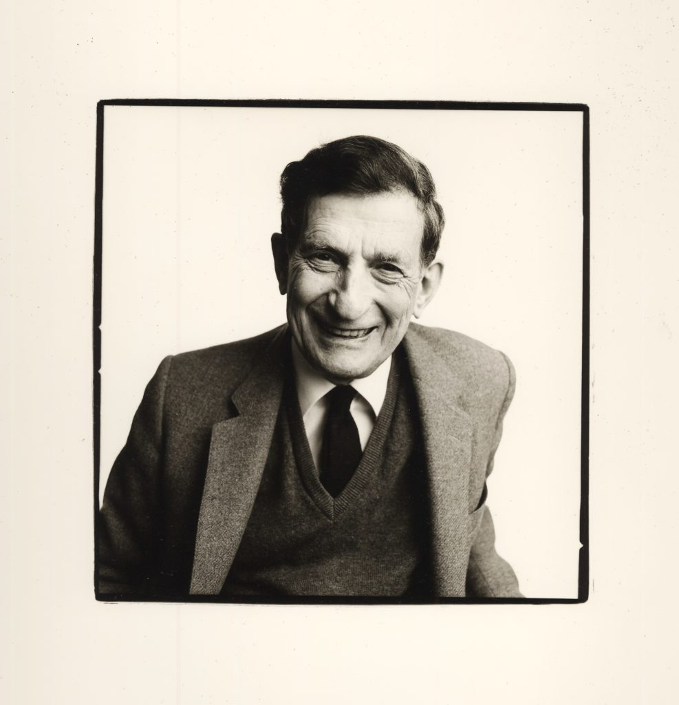 Black and white photo showing a smiling David Bohm in suit jacket, shirt, tie and jumper.