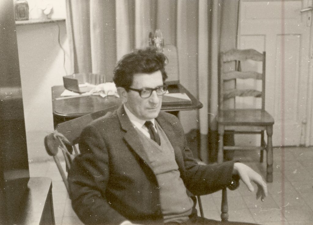 Black and white photo of David Bohm, again in suit jacket, jumper, shirt and tie, this time looking serious and wearing glasses.