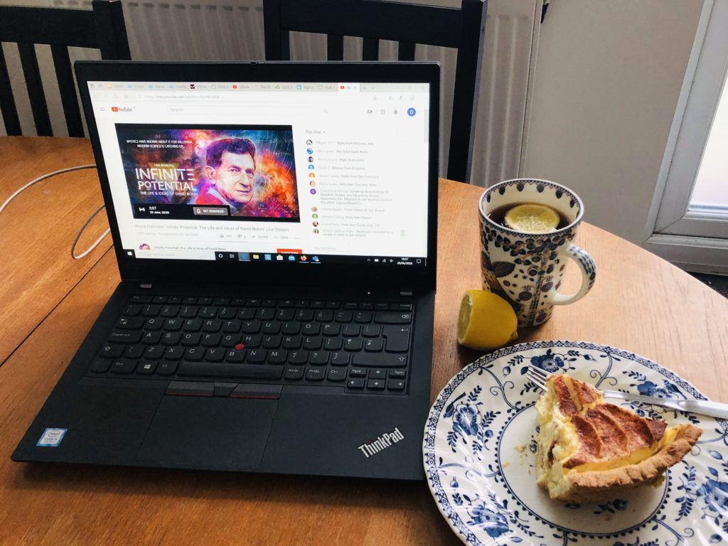 Image of the film poster on a laptop set on a table together with a cup of tea, a lemon and a slice of custard pie.