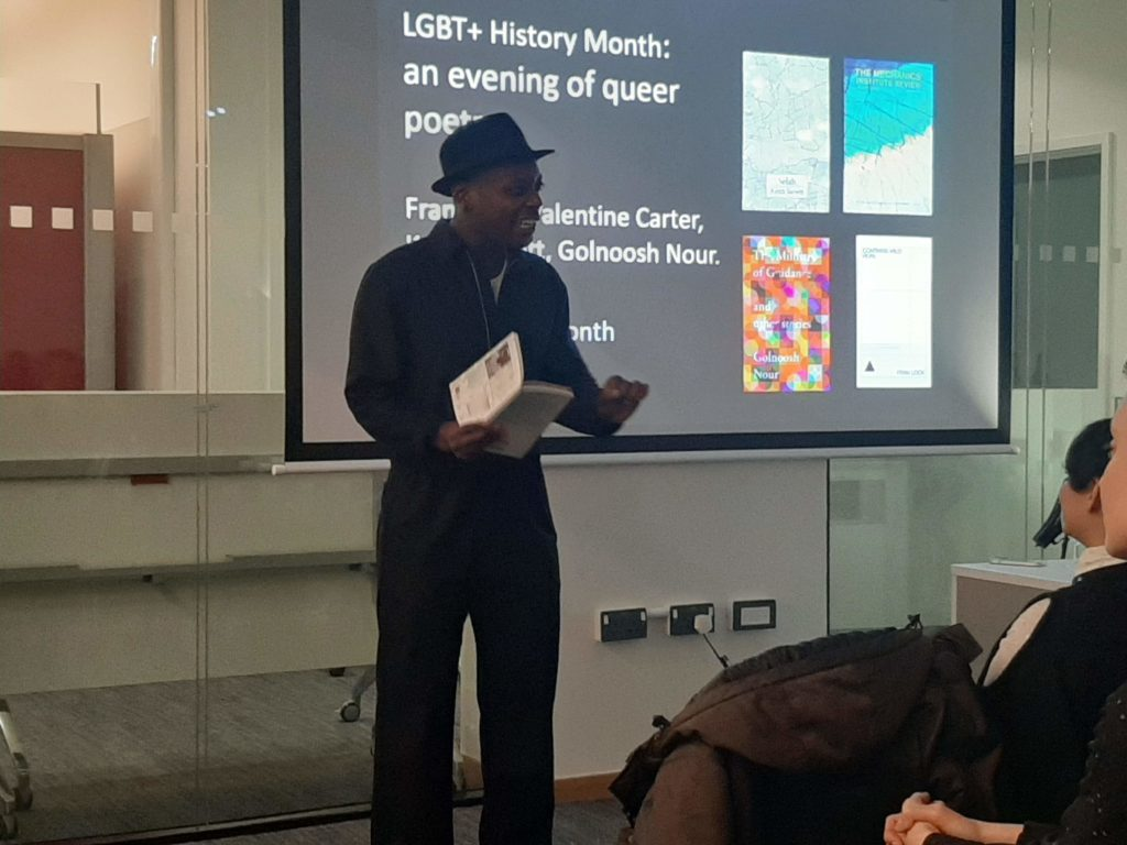 Keith Jarrett's performance at an Evening of Queer Poetry. He is dressed in black and wearing a black trilby.