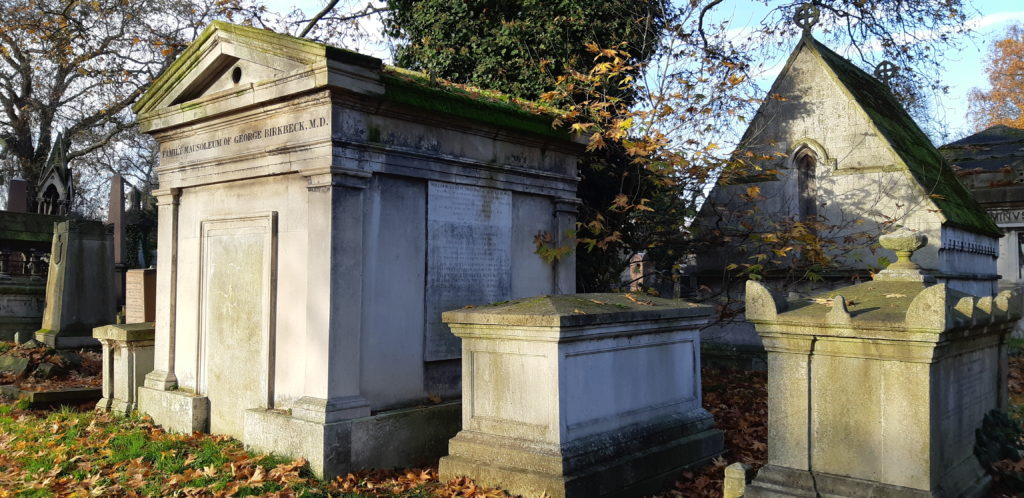 Photo of the Birkbeck mausoleum. A grand stone building with greek style pillars wither side and a pitched roof, also in stone.