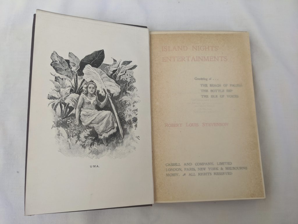 A photograph of the title page spread of Robert Louis Stevenson's Island Nights' Entertainments. On the left-hand page there is an illustration which depicts a girl sitting among some very large leaves, holding up one of them. She looks a little lost, or perhaps fearful.