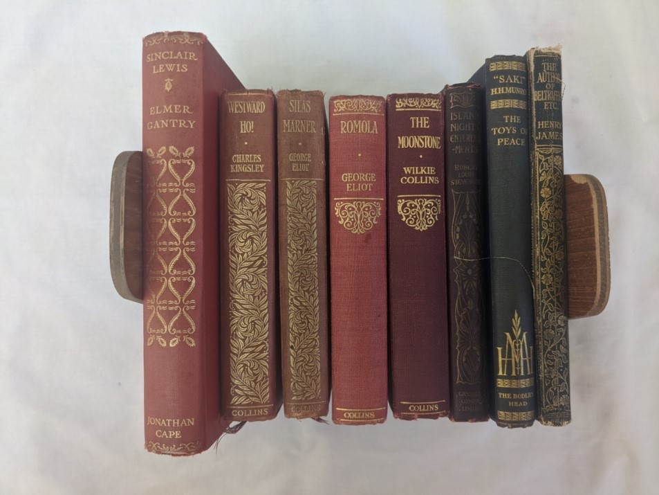 Photograph showing the spines of the eight books discussed in the blog post. The spines feature gilt lettering and decorative patterns.