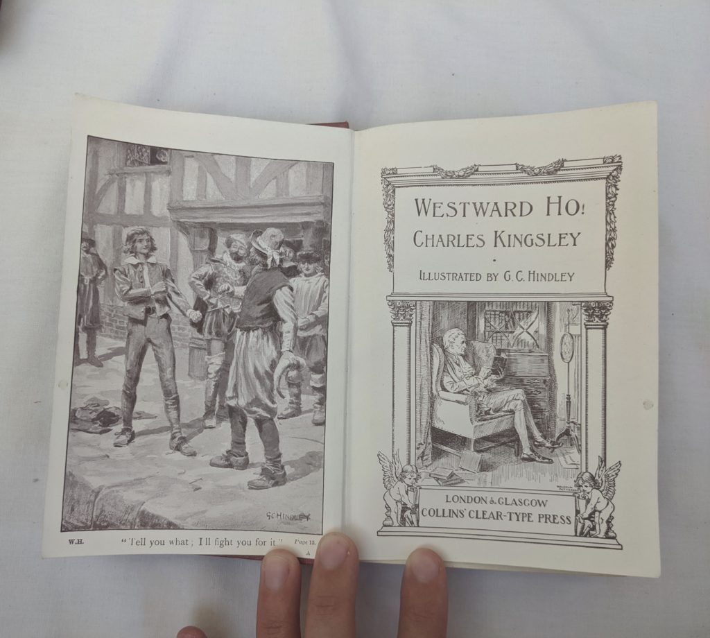 Photo of the illustrated title page spread of Westward Ho! The left-hand page depicts a scene from the book. The title page shows a man sitting in an arm chair by the fire, reading a book.