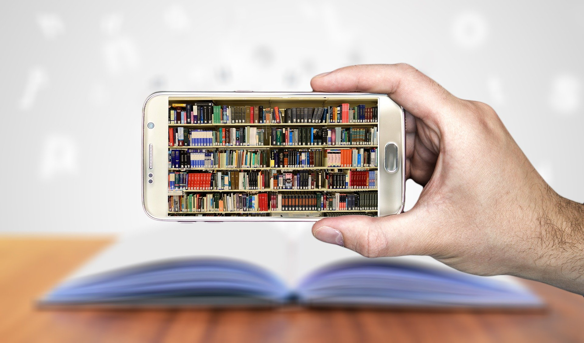 The image shows a hand holding up a smartphone with a photograph of library bookshelves on the screen. In the background, out of focus, is a desk with an open book on it.