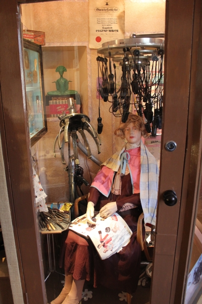 Display at Nidderdale Museum including a mannequin with an early electric hair curler