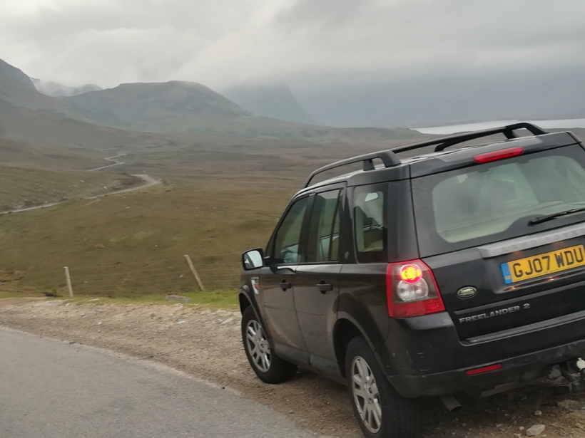 Land Rover parked beside the road to Gairloch. The road winds into the distance with a view of mountains and clouds