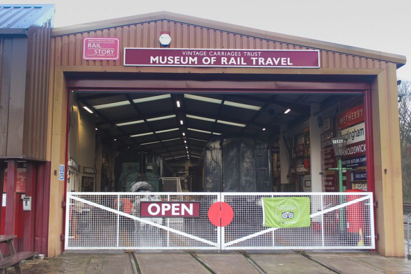 Exterior of Museum of Rail Travel, Keighley. Visible are a locomotive, numerous signs, and a lamp post