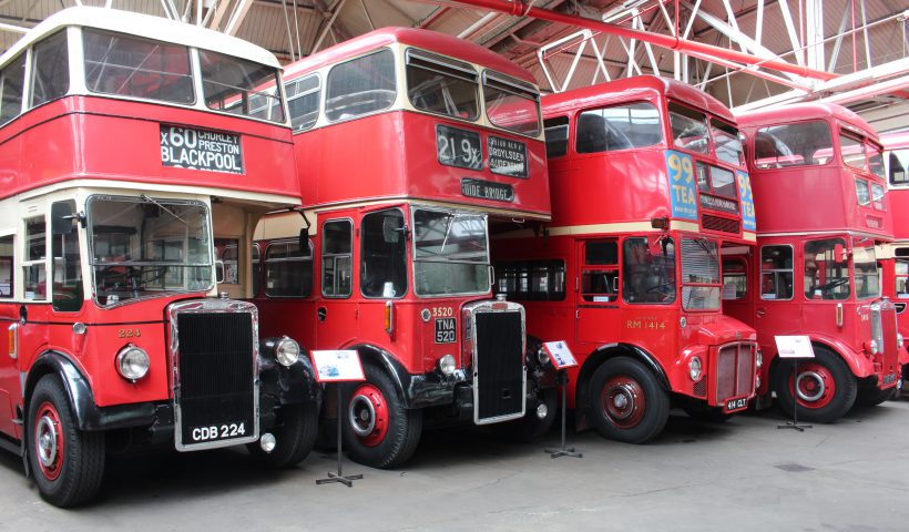 Four red double decker buses in a row inside a garage