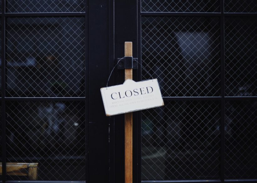 Black glazed doors with a closed sign hanging from the wooden handle