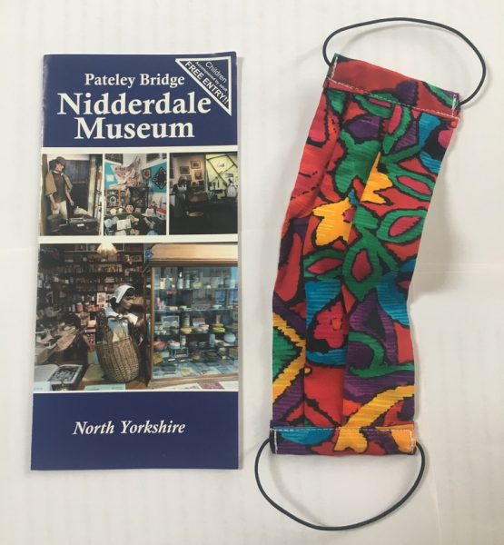 A colourful fabric facemask and a leaflet for Nidderdale Museum