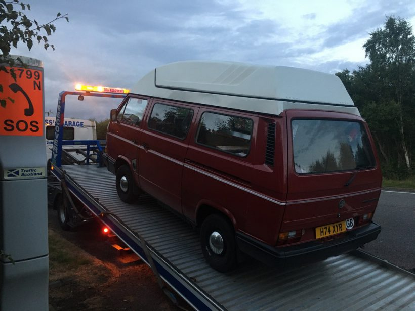 A red VW camper van being winched onto a trailer