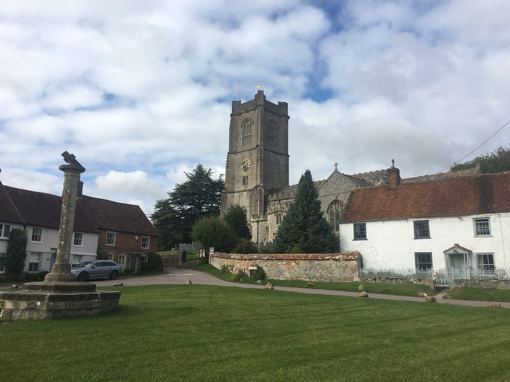 Aldbourne village green. A war memorial on the left, houses to left and right, and the church with a large tower in the centre, at the top of a slight rise.