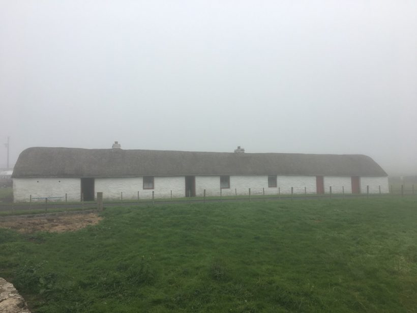 Laidhay Croft Museum, a single storey white building with a thatched roof, seen through a light mist.