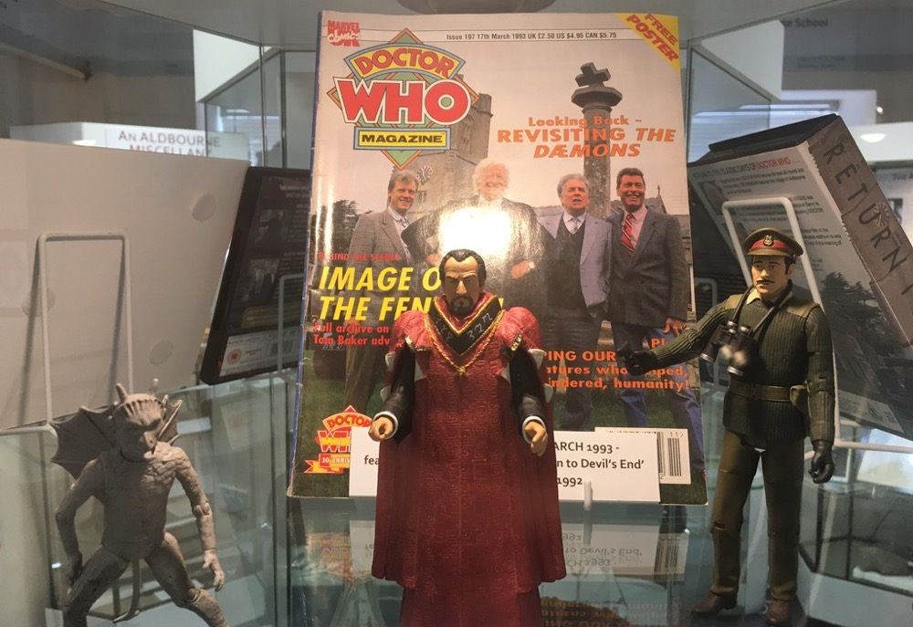 A display of Dr Who memorabilia at Aldbourne Heritage Centre. A grey demon with horns, the Master in an embrodered red robe, a soldier wearing Khaki and binoculars. Behind them is a copy of Dr Who magazine commemorating the making of the series The Daemons.