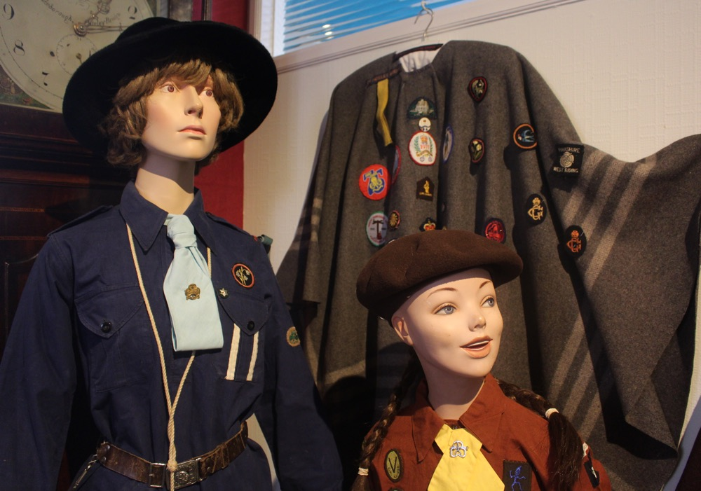 Two mannequins wearing girl guide and brownie uniforms at Nidderdale Museum. A woolen shawl hangs behind them decorated with various cloth badges.