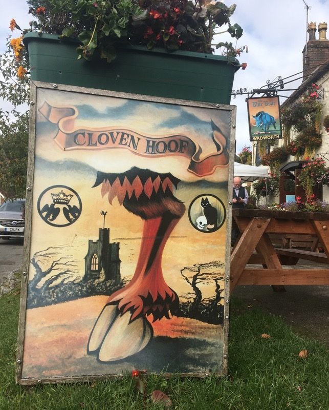 Pub sign The Cloven Hoof on the grass outside The Blue Boar pub in Aldbourne.