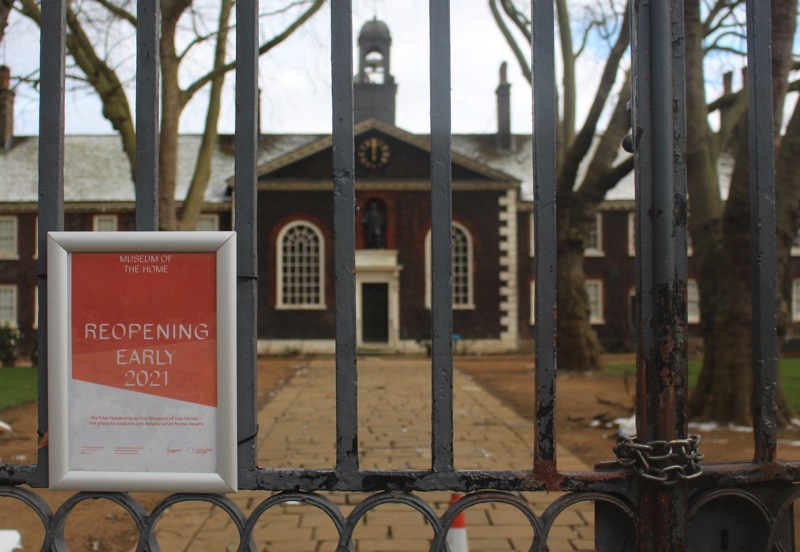 The Museum of the Home in East London viewed through its closed gates. A red and white sign fixed to the gates says 'Reopening early 2021'. The gates are closed with a heavy chain.
