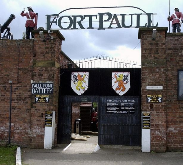 Entrance gates at Fort Paull. Brick walls stand either side of black gates hung with heraldic shields. Two lifesize soldiers stand on the walls above, either side of a large Fort Paull sign.