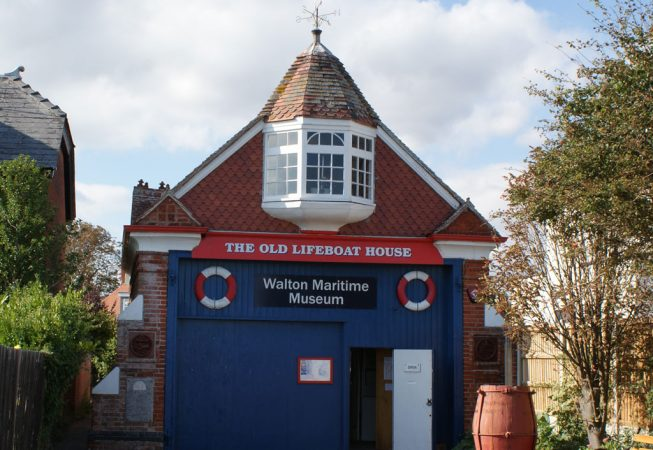 Walton-on-the-Naze Maritime Museum. A building with a blue-painted lower storey and a brick and tile upper storey with a pitched roof and a white-painted oriel window. A red and white sign reads The Old Lifeboat House..