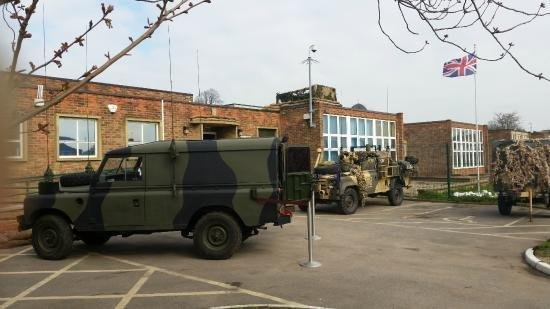 The forecourt of a military building. Jeeps in camouflage are parked and a Union jack flies from a flagpole in the background.
