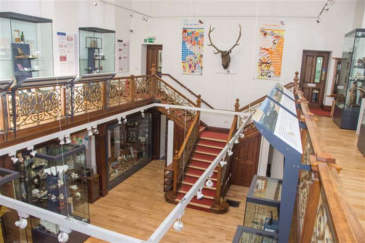 General view of the Falconer Museum. Objects can be seen in glass cases on a gallery and the ground floor. Above a staircase is a mounted stags head.