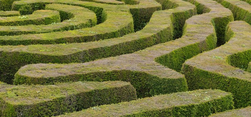 Looking down into a circular maze made of tall green hedges. The centre of the maze can be seen at the upper left.