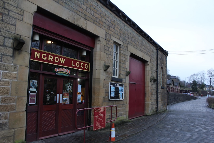 The entrance to Ingrow Loco museum. The building is constructed from large blocks of warm yellow stone and the two doors are painted in burgundy red. A sign above the entrance reads Ingrow Loco in gold on a deep red background. Below is a smaller curved sign that reads Bahamas. A cobbled road leads off to the right where it meets a ramp descending from the side of the building.