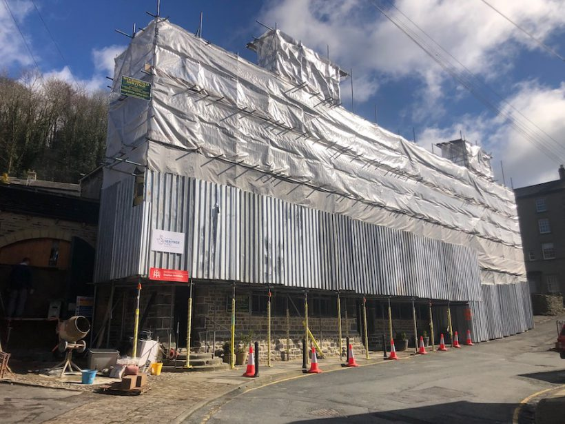 A large building covered in scaffolding, the uuper part of which is wrapped in plastic sheeting that reflects the sunlight. A sign for the Heritage Lottery Fund is affixed to the bottom left of the scaffold. A road runs past, leading off to the right.