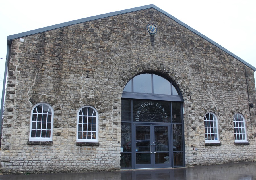 A large stone building with a pitched roof. Large glazed entrance doors with grey frames are topped by an etched sign entitled heritage centre around a line diagram of a wheel. The entrance is flanked by white painted arched windows, two on each side. A small clock is above, just below the angle of the roof.