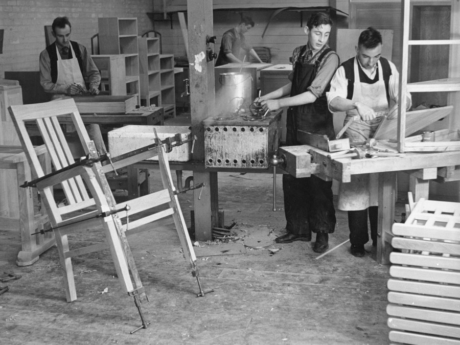 Four men wearing long aprons stand in a furniture workshop. Two are sanding and planing wood, another assembling parts, a third appears to be preparing varnish. A chair stands on its back feet in the foreground, its frame held together with long metal clamps.