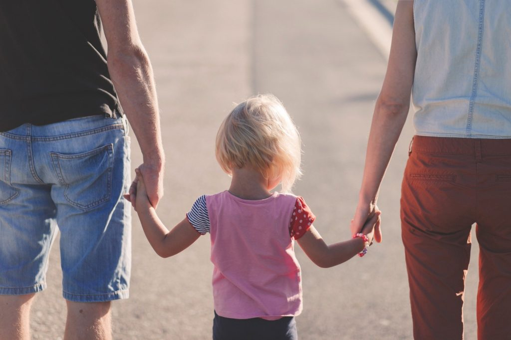A child walking with her parents.