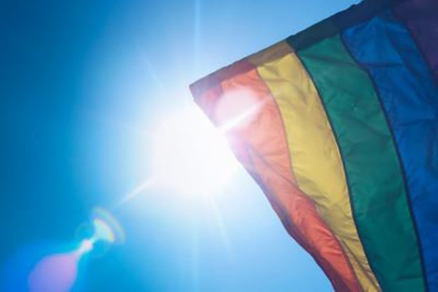 The Pride Rainbow flag partially covering the sun in the sky